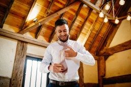 groom getting ready at his barns and yard wedding