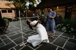 bride doing the limbo on her wedding day at barns and yard